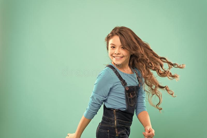 Enjoying her favorite hairstyle. Adorable girl with curly hairstyle waving on blue background. Small cute girl with long royalty free stock image