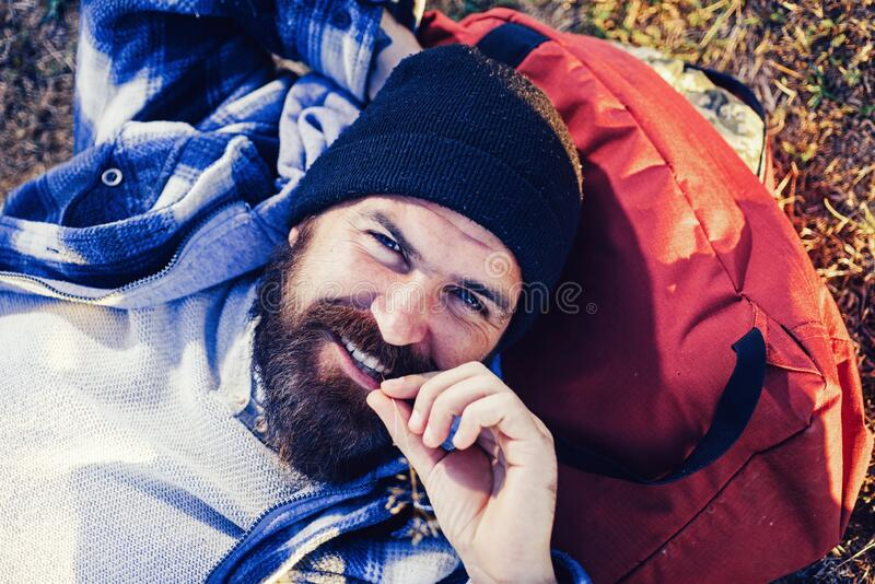 Enjoying his travel. Happy travel man with long beard relaxing on backpack. Bearded hipster smiling during his vacation stock image