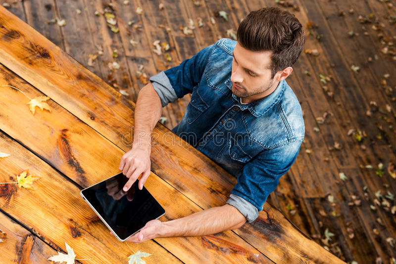 Enjoying his work outdoors. Top view of confident young man working on digital tablet while sitting at the wooden table outdoors stock photo