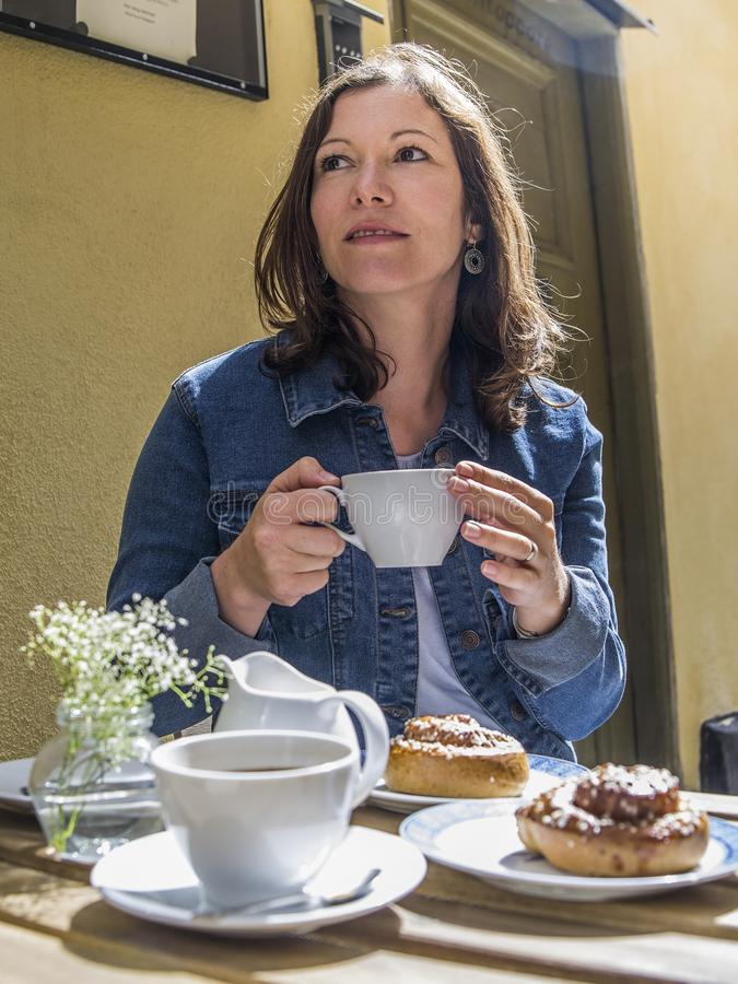 Enjoying Kanelbulle and coffee at outdoor cafe in Stockholm royalty free stock photos