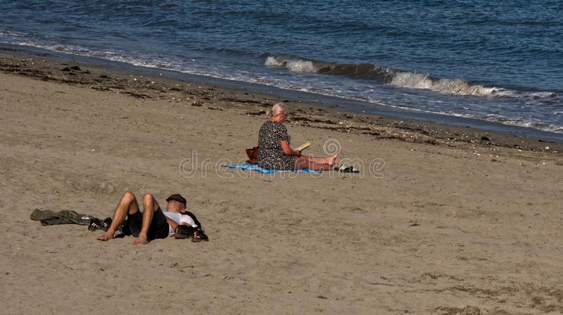 Enjoying the late summer early autumn sunshine in Cornwall in early September 2019. Enjoying the late summer early autumn sunshine, beach goers rest on the beach stock image