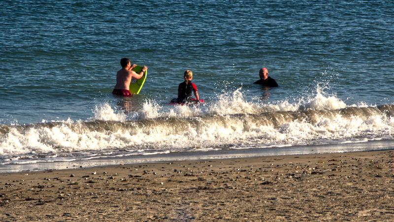 Enjoying the late summer early autumn sunshine in Cornwall in early September 2019. Enjoying the late summer early autumn sunshine, family playing in the water stock photo