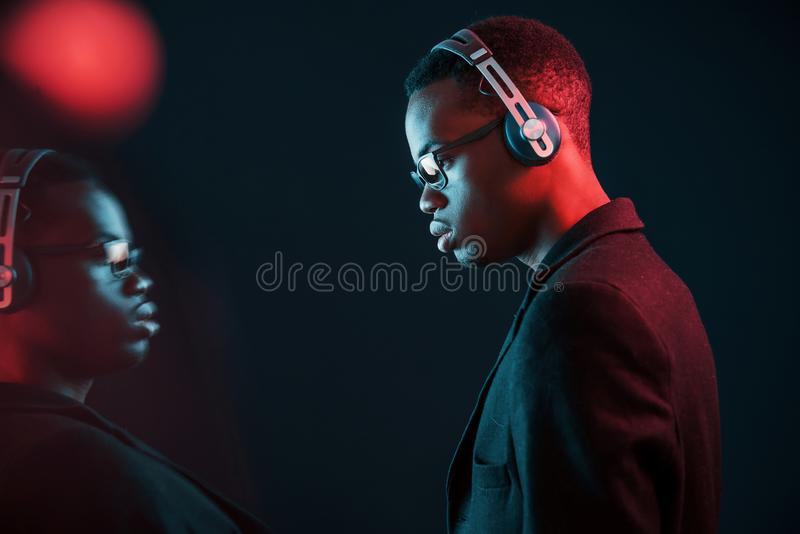 Enjoying listening music in headphones. In glasses. Futuristic neon lighting. Young african american man in the studio royalty free stock photo