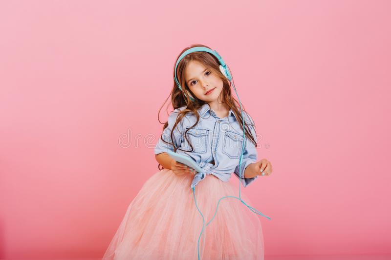 Enjoying lovely music through blue headphones of cute little girl with long brunette hair isolated on pink background stock images