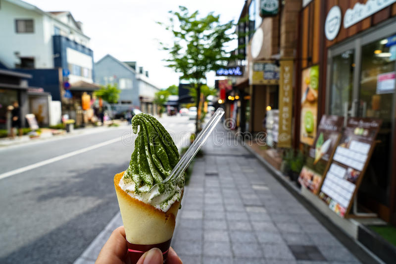 Enjoying milk ice cream soft serve cone with green tea flake pow royalty free stock image