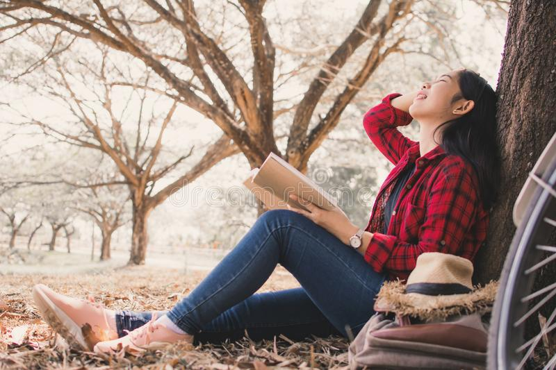 Enjoying moment hipster woman reading a book and sitting under the big tree on park stock photos