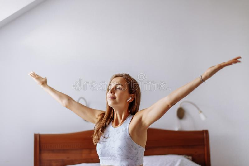 Yoga woman listening to music during morning yoga practice on bed. stock photo