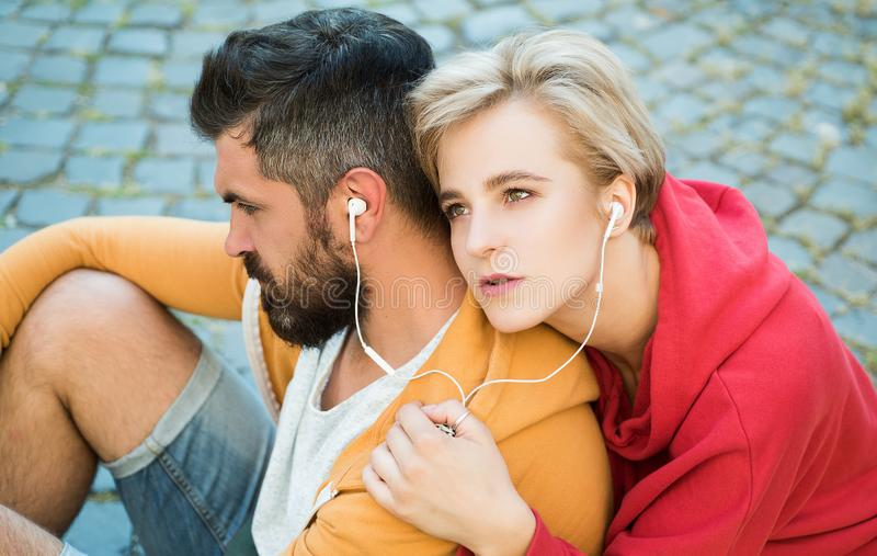 Enjoying music. Youth fashion. Feeling free and stylish. Man and woman modern clothes for youth relaxing outdoors stock images