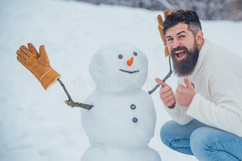 Enjoying nature wintertime. Handsome bearded man, father in winter clothes. Christmas Man and snowman on white snow royalty free stock photo