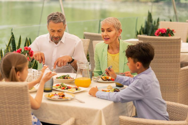 Two children and grandparents enjoying nice morning in restaurant stock image