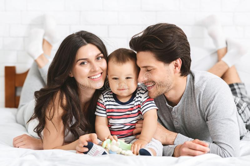 Happy young parents cuddling with adorable baby son on bed royalty free stock image