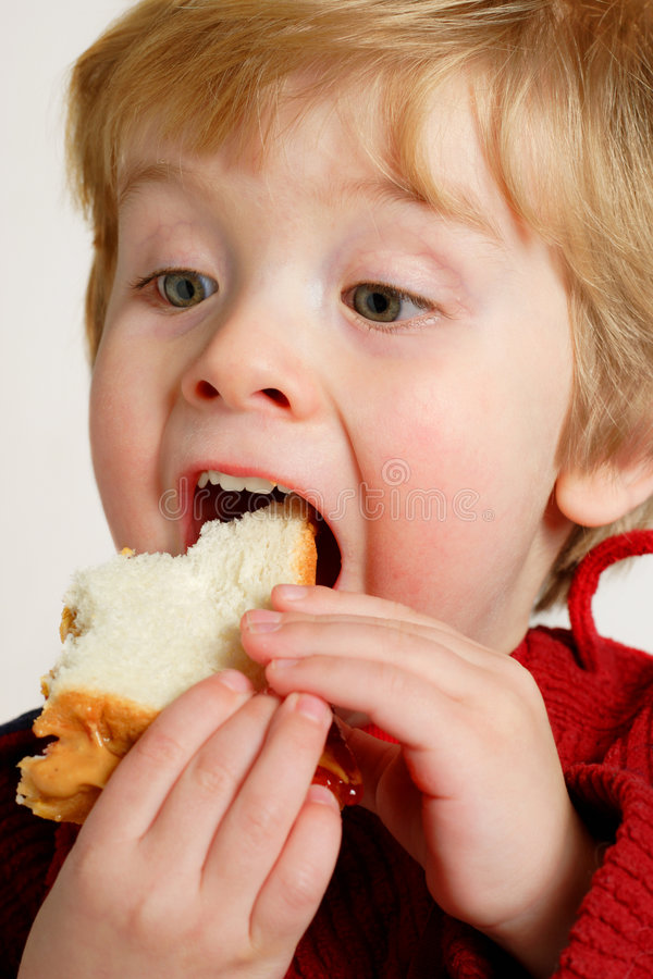 Enjoying a peanut butter and jelly sandwich stock photography
