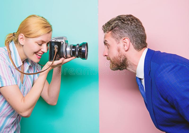 Enjoying photo shoot session. Photographer shooting male model in studio. Pretty woman using professional camera. Businessman posing in front of female royalty free stock image
