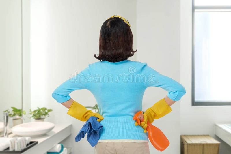 Enjoying Results of Spring Clean. Back view of unrecognizable woman wearing rubber gloves standing at spacious bathroom and enjoying results of spring clean, she royalty free stock photo