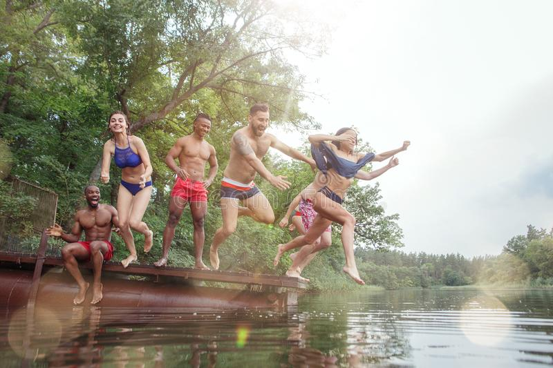 Enjoying river party with friends. Group of beautiful happy young people at the river together stock photo