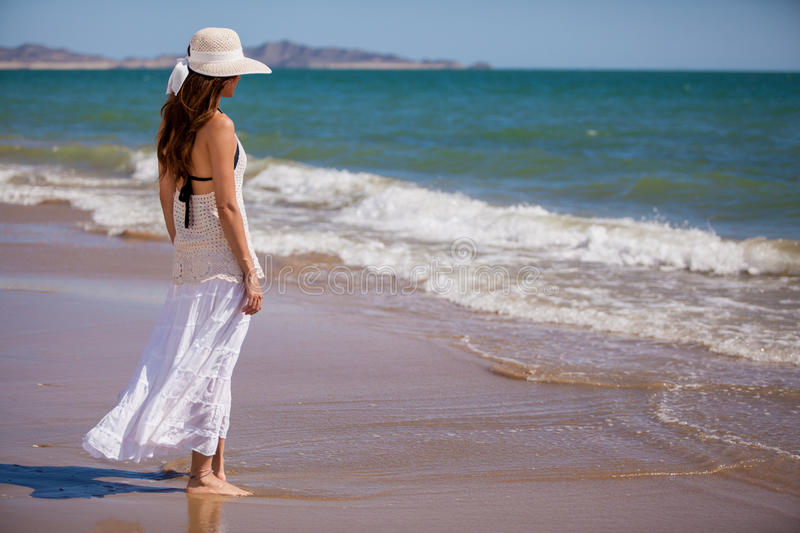 Enjoying the sound of the waves. Beautiful woman wearing a hat relaxing and looking at the sea stock photography