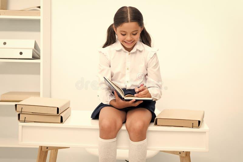Enjoying studying. Girl child reads book while sit on table near pile of books white background. Schoolgirl enjoy royalty free stock image