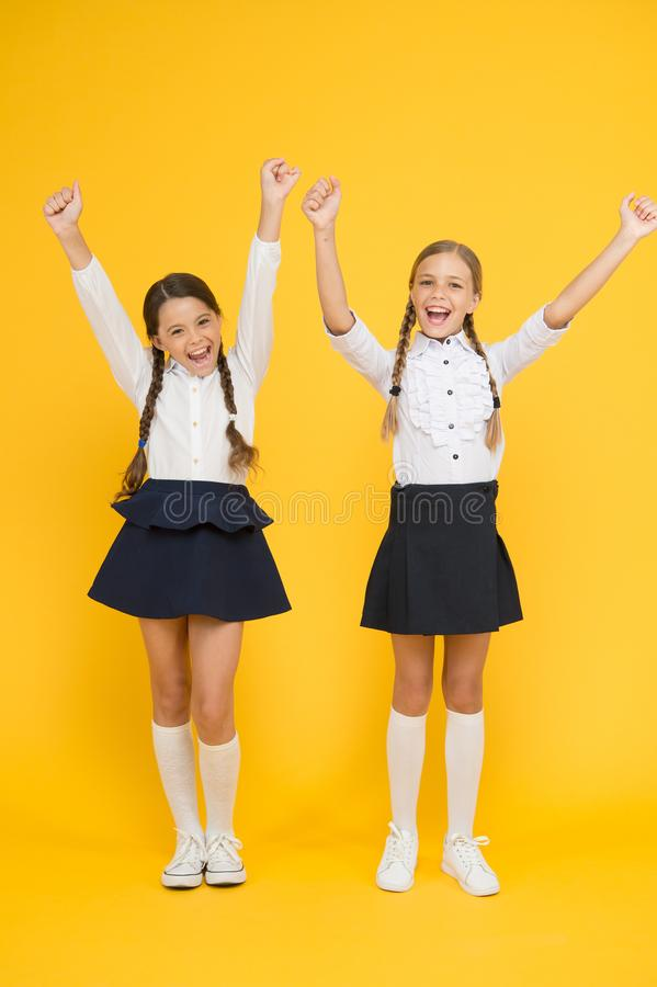Enjoying success. Happy children celebrating success on yellow background. Little schoolgirls being excited about royalty free stock photography