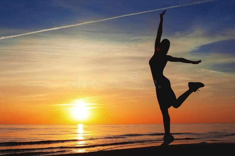 Enjoying the summer sunset. Cheerful woman silhouette dancing on. Enjoying the summer sunset. Cheerful slender woman silhouette dancing on the sunset with raised royalty free stock photography