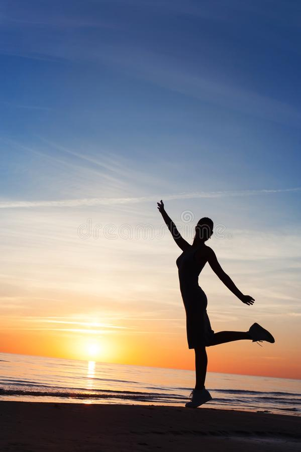 Enjoying the summer sunset. Cheerful woman silhouette dancing on. Enjoying the summer sunset. Cheerful slender woman silhouette dancing on the sunset at blue sky stock photos