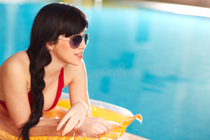 Enjoying summertime. Portrait of lovely woman in bikini and sunglasses lying on mattress stock photo