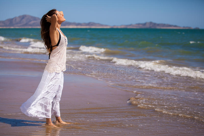 Enjoying a sunny day at the beach. Gorgeous young woman enjoying the warmth of the sun at the beach stock photo