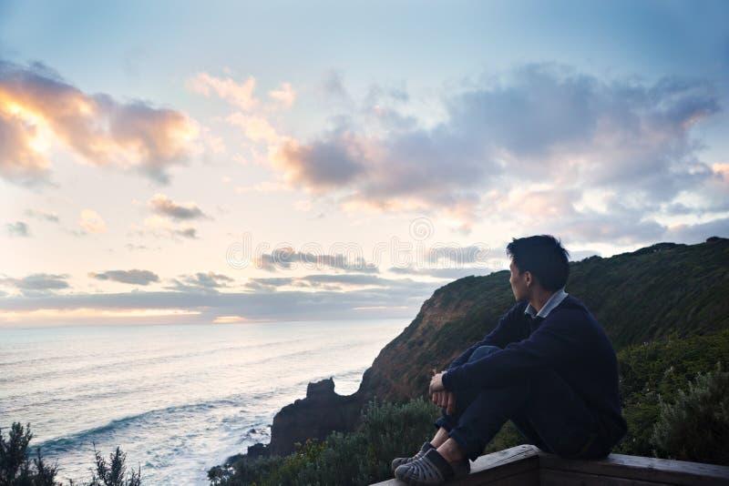 Enjoying sunset. A young man sitting on the edge of wooden border enjoying the sunset stock photo