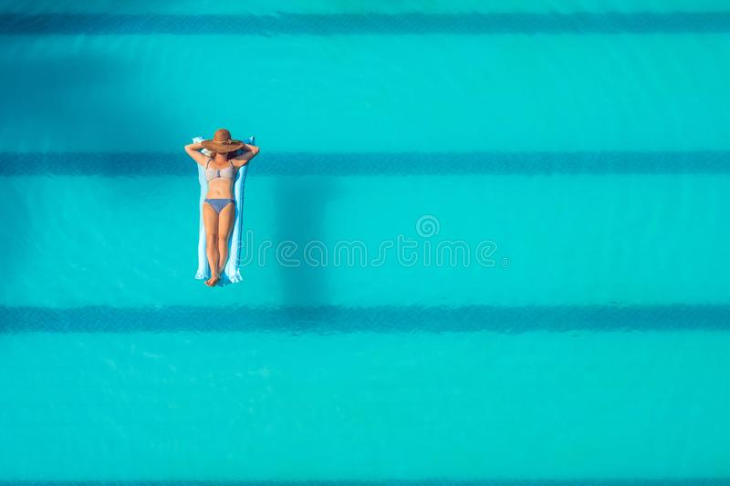 Enjoying suntan. Vacation concept. Top view of slim young woman in bikini on the blue air mattress in the big swimming pool royalty free stock image