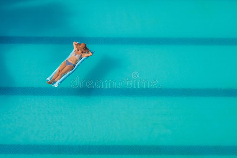 Enjoying suntan. Vacation concept. Top view of slim young woman in bikini on the blue air mattress in the big swimming royalty free stock photo
