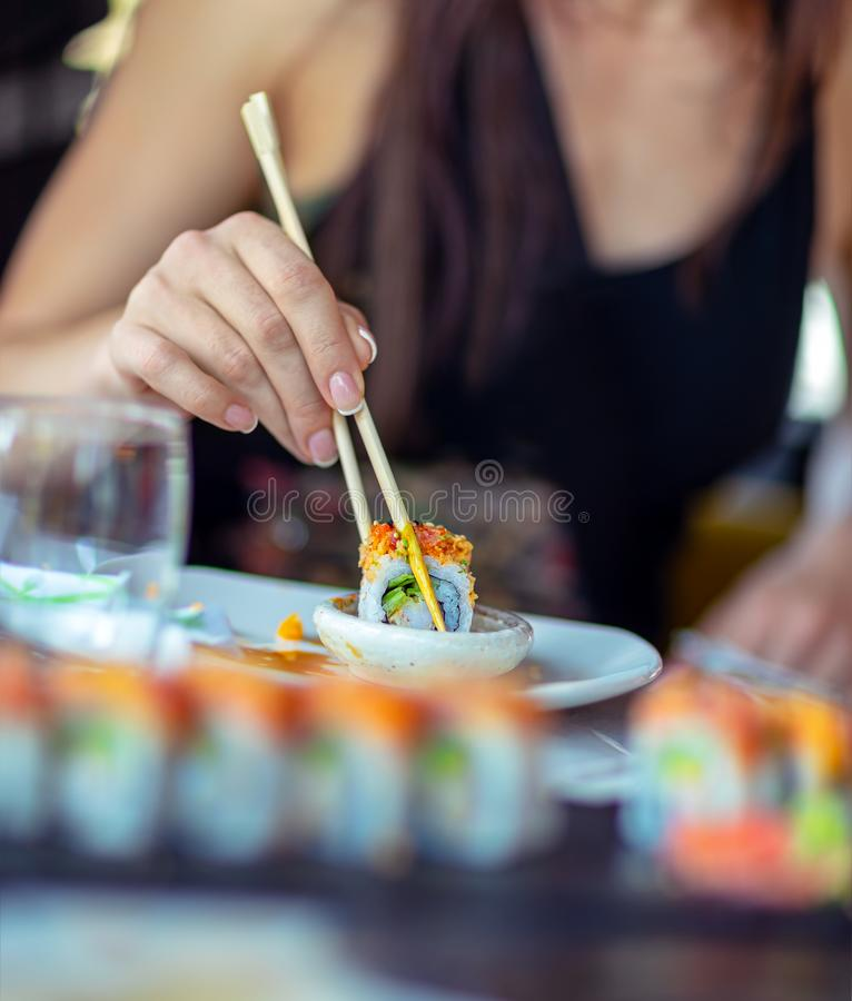 Enjoying sushi. Woman in a restaurant dines sushi, dips a slice of a rolls in soy sauce, trendy Asian food, a tasty oriental cuisine royalty free stock photo