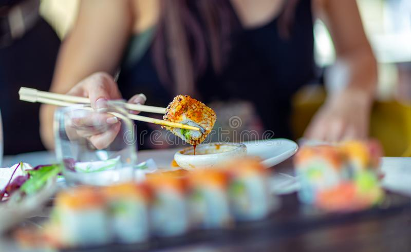 Enjoying sushi. A woman in a restaurant dines sushi, dunks a slice of rolls in soy sauce, trendy Asian food, a tasty dietary dish royalty free stock image