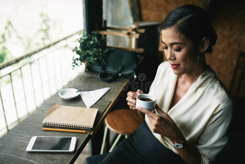 Enjoying taste and aroma. Beautiful Vietnamese business woman smelling coffee before drinking stock photography