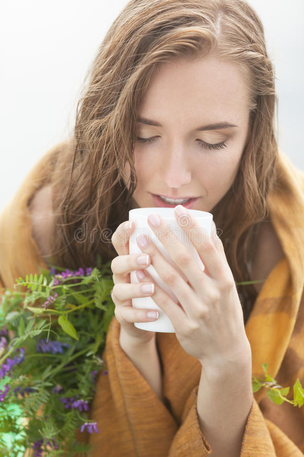 Enjoying tea with herbs. Freezing and wet woman in plaid enjoying tea with herbs royalty free stock images