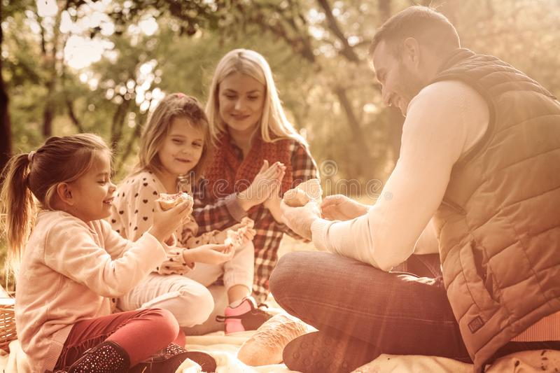 Enjoying their family picnic. Young family having picnic on autumn day. Close up stock photography