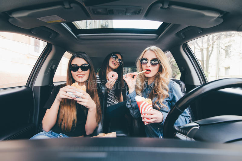 Enjoying their lunch in the car. Four beautiful young cheerful women looking at each other with smile and eating take out food whi royalty free stock photography