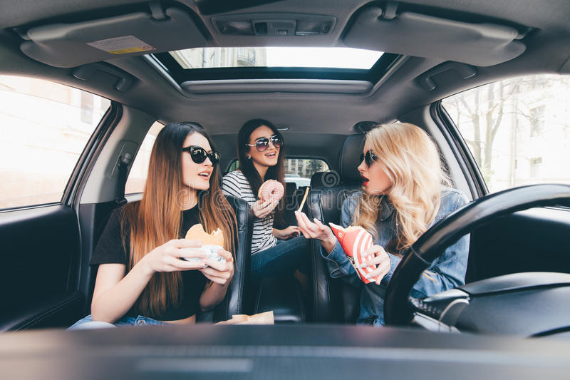 Enjoying their lunch in the car. Four beautiful young cheerful women looking at each other with smile and eating take out food whi stock image