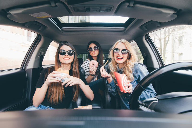 Enjoying their lunch in the car. Four beautiful young cheerful women looking at each other with smile and eating take out food whi stock images