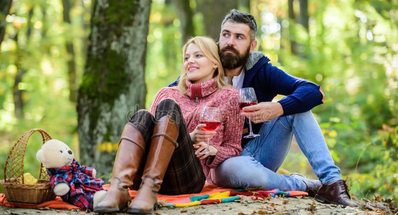Enjoying their perfect date. Happy loving couple relaxing in park together. Romantic picnic with wine in forest. Couple royalty free stock photography