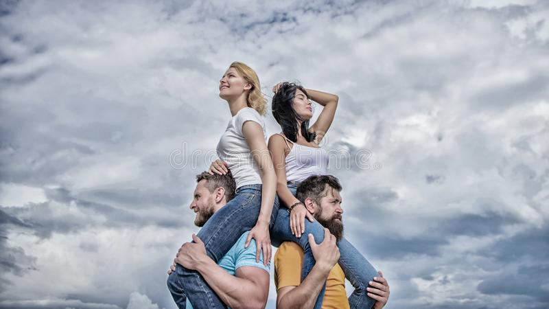 Enjoying themselves. Happy men piggybacking their girlfriends. Loving couples enjoy fun together. Loving couples having. Fun activities outdoor. Playful couples royalty free stock image