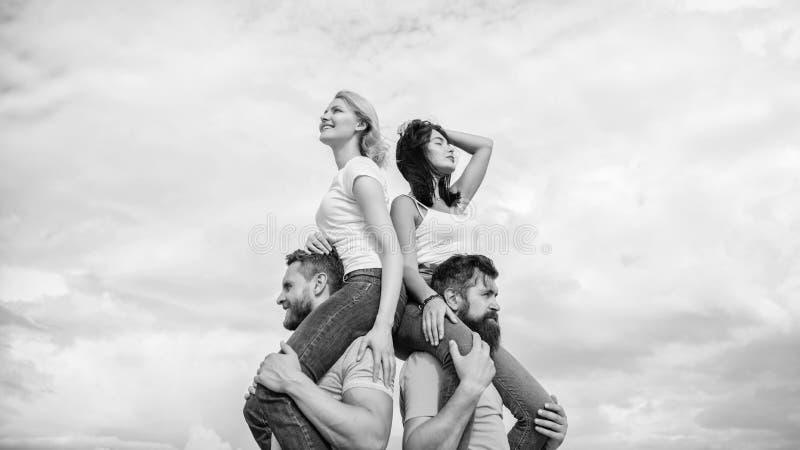Enjoying themselves. Happy men piggybacking their girlfriends. Loving couples enjoy fun together. Loving couples having stock photos