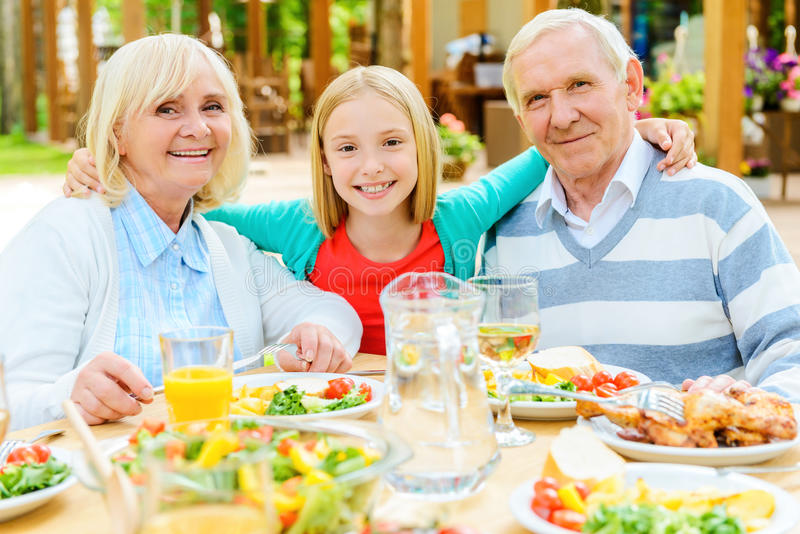 Enjoying time with grandparents. Happy little girl embracing her grandparents and looking at camera while sitting at the dining table outdoors together royalty free stock photo