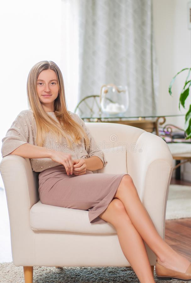 Beautiful young smiling woman is sitting in comfortable chair at home stock image