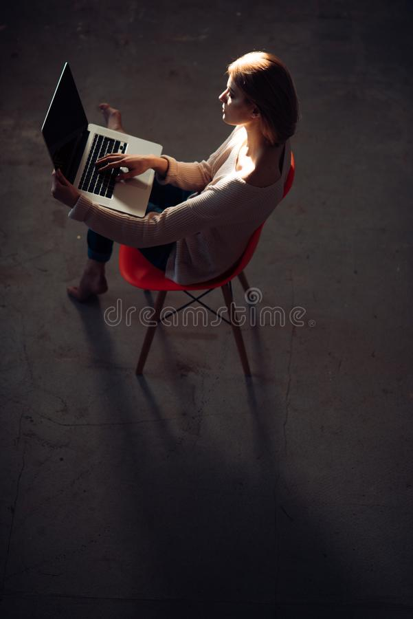 Enjoying time at home. Beautiful young woman working on laptop sitting in comfortable chair at home. stock photo