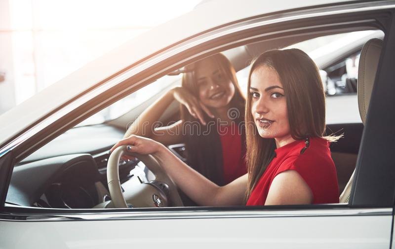 Enjoying travel. Beautiful young girl twins sitting on the front passenger seats and smiling while posing on camera.  stock photography