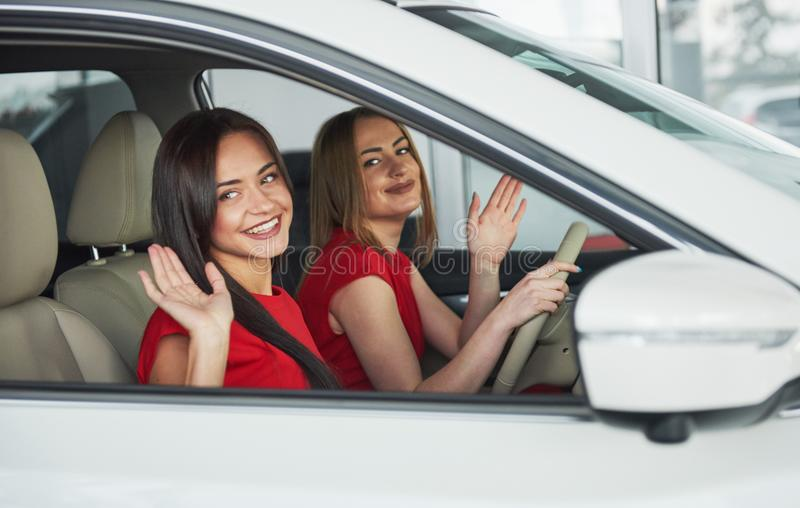 Enjoying travel. Beautiful young girl twins sitting on the front passenger seats and smiling while posing on camera. Enjoying travel. Beautiful young girl twins royalty free stock photography