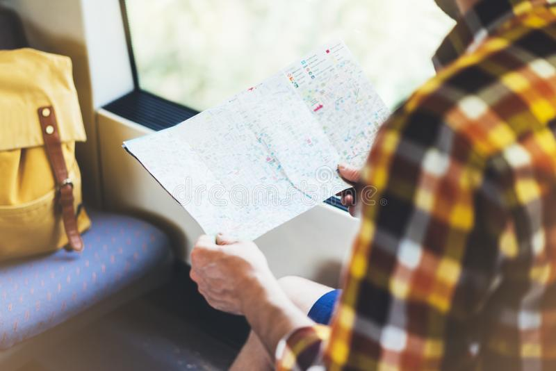 Enjoying travel. Young hipster smile man with backpack traveling by train sitting near the window holding in hand and looking map royalty free stock photos