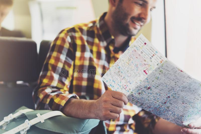 Enjoying travel. Young hipster smile man with backpack traveling by train sitting near the window holding in hand and looking map. Tourist in summer shirt royalty free stock images