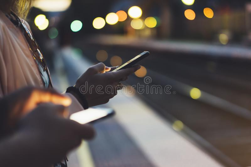 Enjoying travel. Young woman waiting on station platform on background light electric moving train using smart phone in night royalty free stock photo