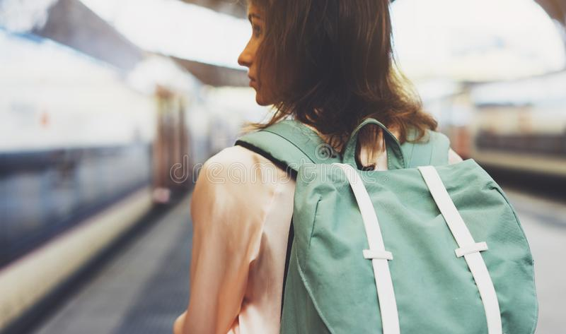 Enjoying travel. Young woman waiting on the station platform with backpack on background electric train. Tourist plan route. Of railway, railroad transport stock photo