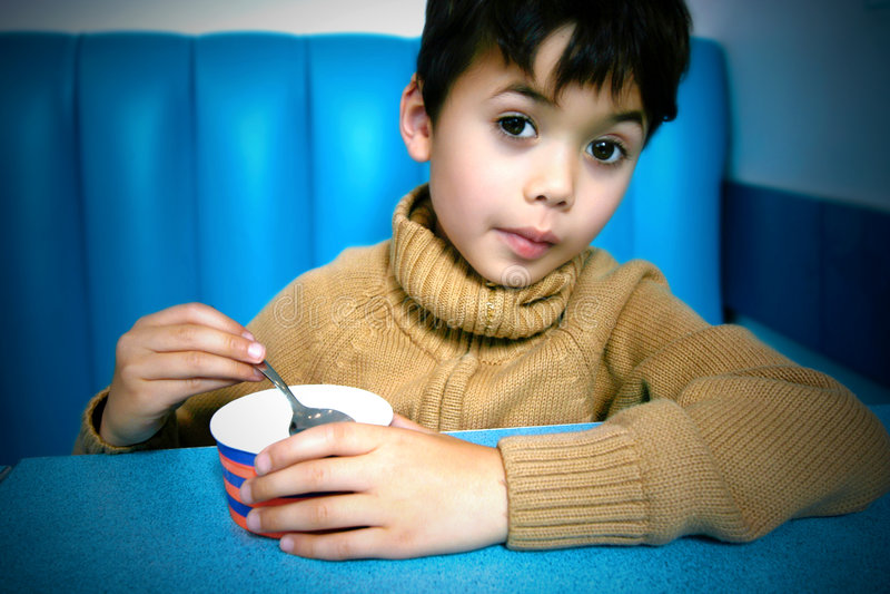 Enjoying a tub of icecream. Young boy enjoying a tub of icecream at the restaurant stock photos